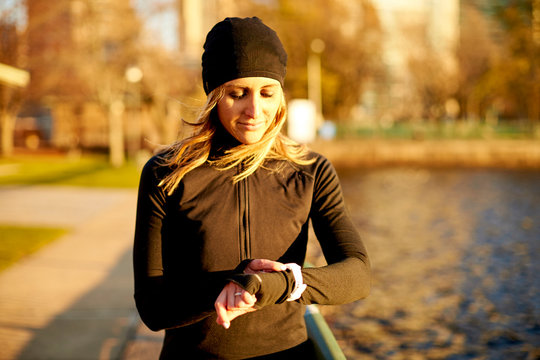 An athletic woman checking her run stats on her smart watch.