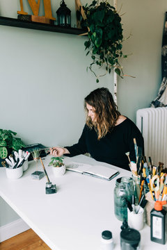Stock photo of a lettering artist at work with her sketch book.