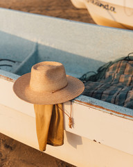 A traveller's hat rest along side a fishing boat
