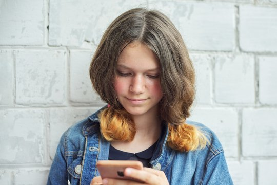 Portrait of beautiful smiling teenage girl of 14, 15 years old with smartphone