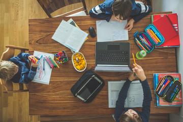 Three children, sitting around the table, writing school tasks while homeschooling