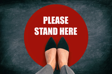 Fotorolgordijn Hoogte schaal COVID-19 Coronavirus message asking supermarket customer to stand in space. Top view of feet standing in red circle with text in public space practicing social distancing. Blackboard background.