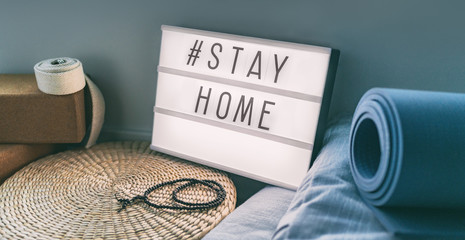 Papiers peints Londres Coronavirus Yoga at home sign lightbox with text hashtag #STAYHOME glowing in light with exercise mat, cork blocks, strap meditation pillows. COVID-19 banner to promote self isolation staying at home.