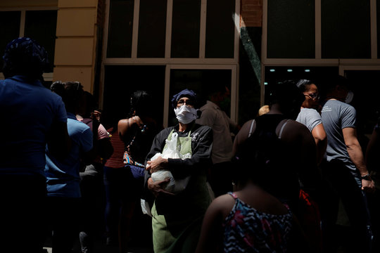 A woman wearing a protective face mask buys yoghurt at a state store amid concerns about the spread of the coronavirus disease (COVID-19), in Havana