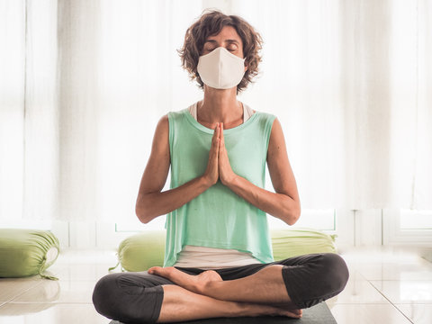 meditating woman wearing a medical face mask to protect from corona virus covid-19 in crossed legged lotus and praying namaste position on a yoga mat in a studio