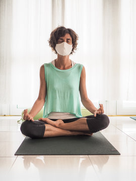 meditating woman wearing a medical face mask to protect from corona virus covid-19 with closed eyes, in crossed legged lotus position on a yoga mat in a studio
