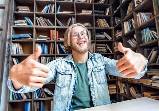 Young bearded smiling student man teen hipster blogger vlogger glasses look at camera hold thumbs up cool gesture shoot vlog youtube channel home library encourage followers stream online.