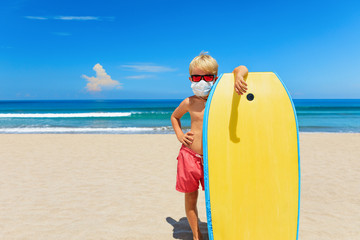 Young surfer wearing sunglasses, protective mask on sea beach with body board. Summer tours, cruises cancellation due to coronavirus COVID-19 epidemic. Safe travel destinations for family vacation. Fototapete