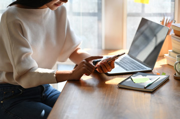 Cropped image of beautiful woman working as secretary holding/using a black blank screen smartphone while sitting in front her blank screen computer laptop over comfortable living room as background.