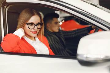 Couple in a car salon. Family buying the car. Elegant woman with her boyfriend.