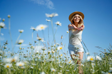 Girl in a field with flowers. Beautiful young woman in a field with daisies.  Fotobehang