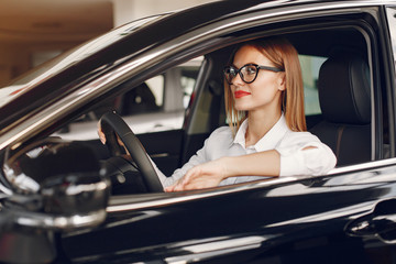 Lady in a car salon. Woman buying the car. Elegant woman in th ecar interior.