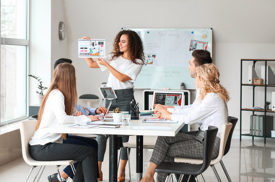 Female interior designer teaching young people in office