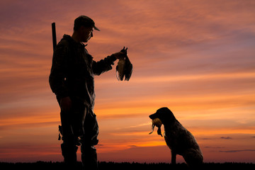 a hunter and his dog with downed ducks at sunset
