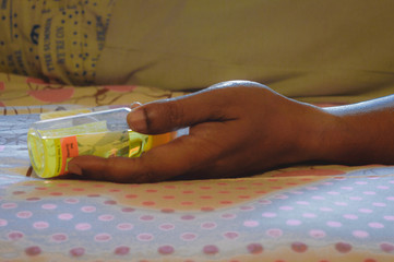 Close up human hand of dead person with medicine bottle lying on death bed due to drug narcotic overdose. Concept of poisoning and suicide. World suicide prevention day background theme photography.