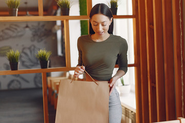 Beautiful girl in a cafe. Lady with shopping bags. Woman in a gray top.