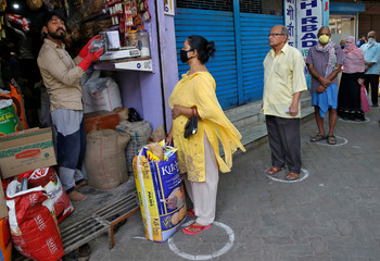 People queue standing in circles drawn to maintain safe distance as they wait to buy grocery items during a 21-day nationwide lockdown to limit the spreading of Coronavirus disease (COVID-19), in Kolkata