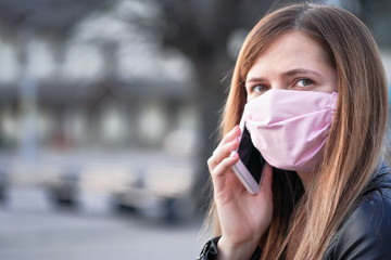 Young woman with hand made face nose mouth mask talking on her mobile phone, close portrait, space on left side. Can be used during coronavirus covid-19 outbreak prevention
