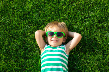 Happy child lying on spring green grass