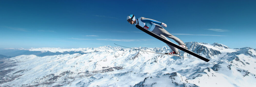 Ski jumping over the mountain slope with blue sky