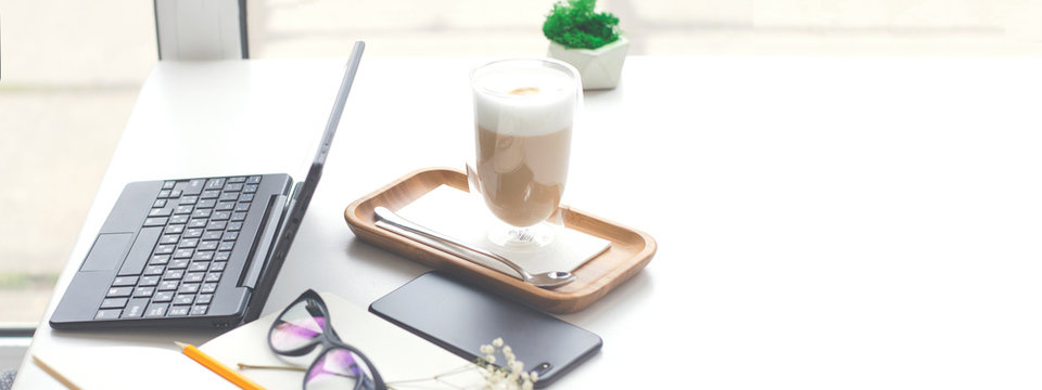 Desktop with laptop, smartphone, notepad and coffee maker.
