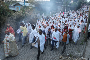 Ethiopian Orthodox faithful hold candles as they receive a blessing from a priest with an incense smoke in Addis Ababa