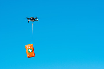 multicopter drone flying with a first aid kit isolated on a blue sky, emergency medical care concept