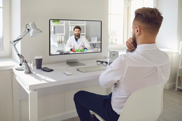 Online doctor.A man talking to a doctor online on a computer on a desk in an office. Online medical...