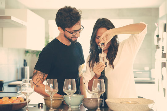 Happy couple celebrating special date and opening wine bottle in kitchen. Young man and woman in casual meeting indoors. Celebration at home concept