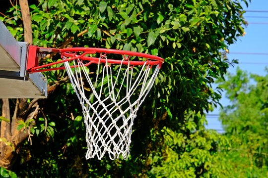 Outdoor basketball hoop with net at the backyard of the house.