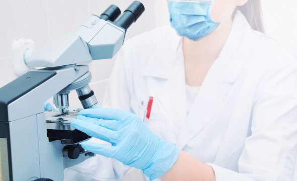 young medical scientist researching virus on a microscope in laboratory