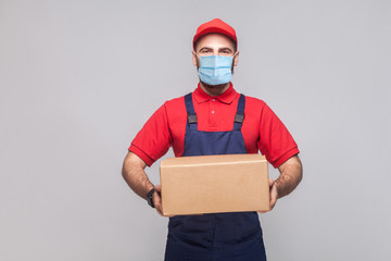 Delivery on quarantine. Portrait of young man with surgical medical mask in blue uniform and red...