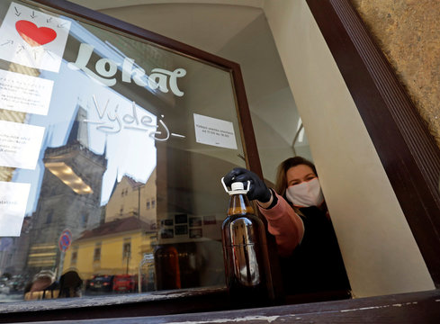 A waitress passes a plastic bottle of beer to a customer in Prague