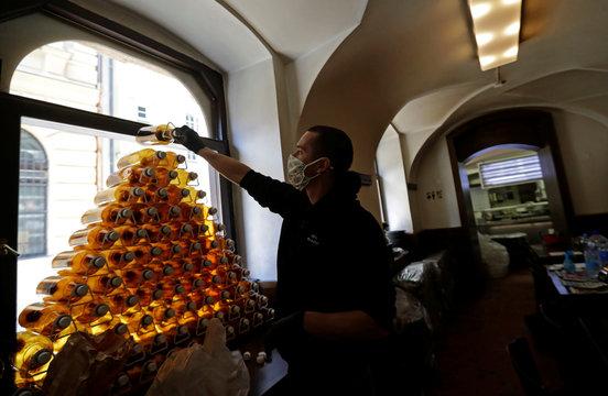 A bartender prepares plastic bottles inside of a closed pub in Prague