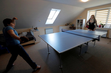Kseniya and Ilya Gushchin, students, play table tennis as they have a break during their online lessons, following the outbreak of the coronavirus disease (COVID-19), at their home in the village of Kolodishchi
