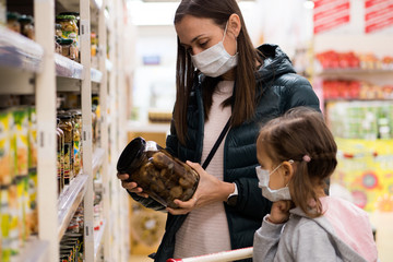 Young woman with child girl in medical masks buys a canned food in grocery department at supermarket. Virus epidemic concept.
