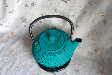 Turquoise cast iron teapot on beige background, top view