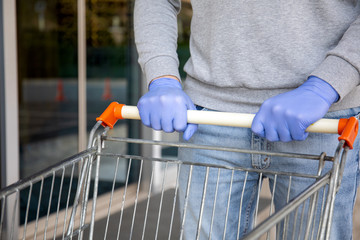 man in protective disposable gloves holding food trolley in store