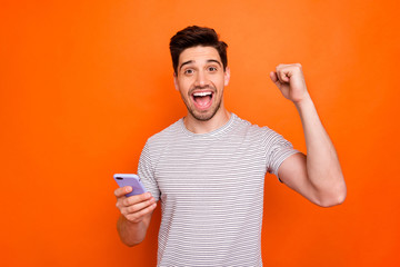 Photo of funky cool guy cheerful good mood hold telephone raise fist celebrate first startup...