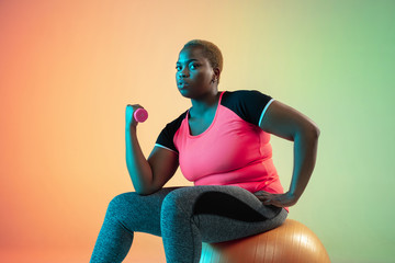 Young african-american plus size female model's training on gradient background in neon light....