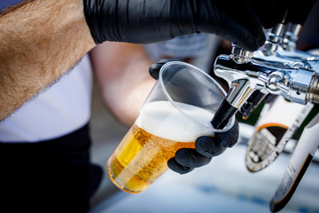 Bartender in black gloves pours beer into a disposable plastic glass