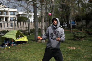 A man plays with balls in the park, during the intercity ban, amid fear of coronavirus disease (COVID-19), in Tehran