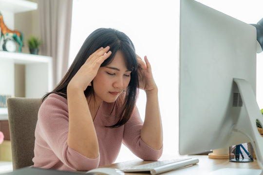 Candid of young Asian single business woman stress out with project business plan on computer laptop or notebook at home office. Asian people occupational burnout syndrome concept..