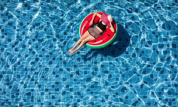 Top view of woman lay on balloon in pool