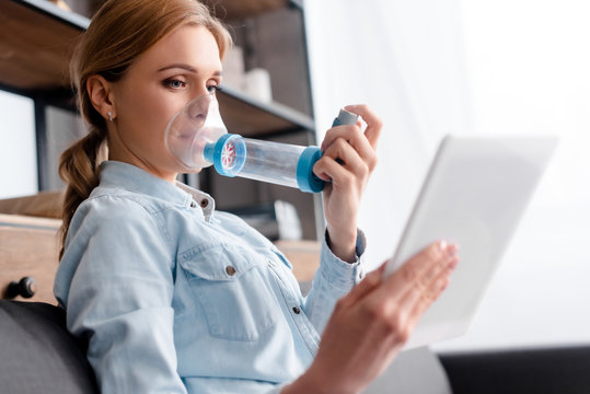 selective focus of sick woman using inhaler with spacer and holding digital tablet