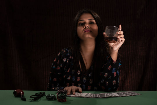 Young Indian plus size Bengali brunette woman in western dress throwing cards on a casino poker table in black copy space studio background. Indian lifestyle and fashion.