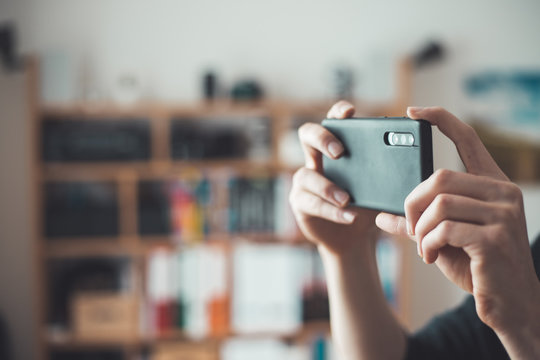 Social media content production with the smartphone. Close up of black smartphone camera lens indoors.