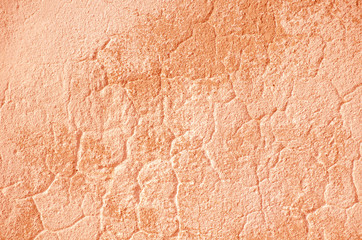 Fragment of old house wall close-up. Pink background. Peeling plaster on concrete surface. Cracks...