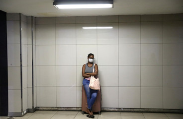 A woman wearing a protective mask rests on her luggage at Park Station ahead of a nationwide lockdown for 21 days to try to contain the coronavirus disease (COVID-19) outbreak, in Johannesburg