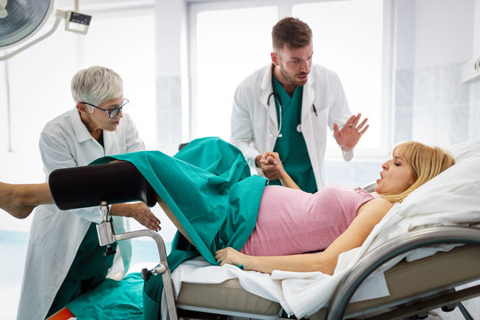 In the hospital woman in labor pushes to give birth, obstetricians assisting